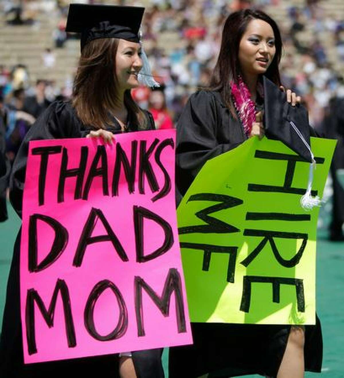 Graduating students Jessica Meurs, left, and Toquyen Truong hold brightly-colored signs while walking to their seats.