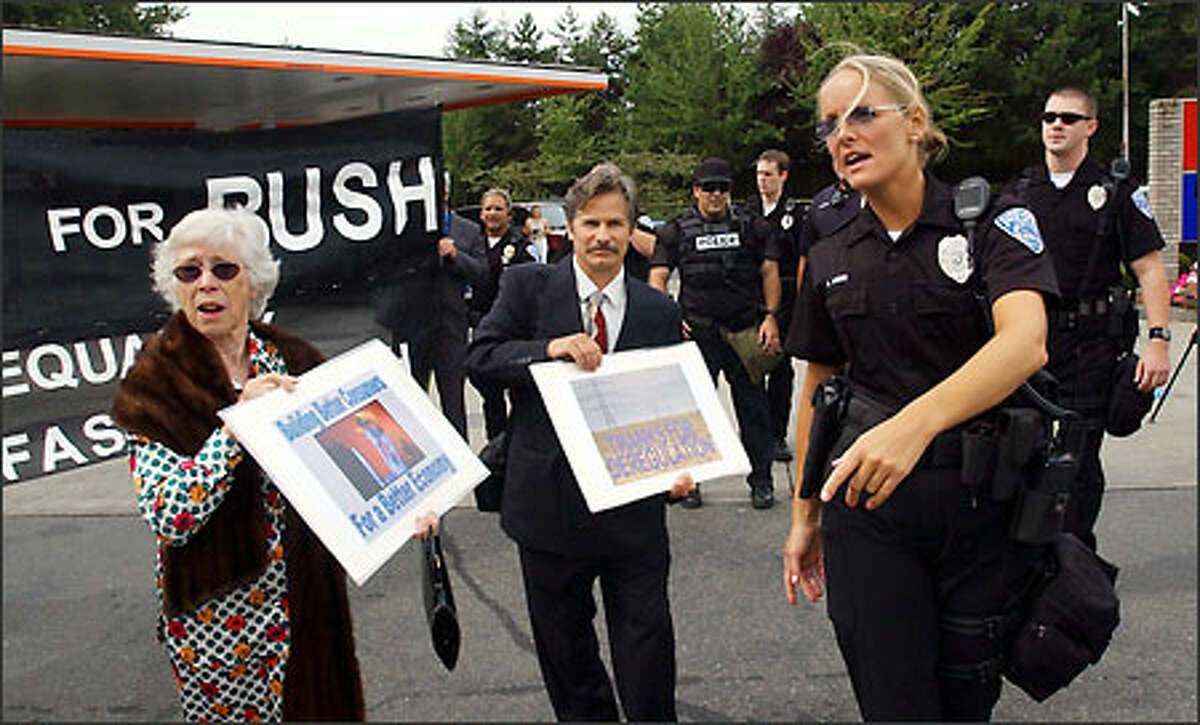 A police officer escorts members of a street theater group calling themselves Billionaires for Bush to a designated protest area in Hunts Point, where President Bush attended a fund-raiser.