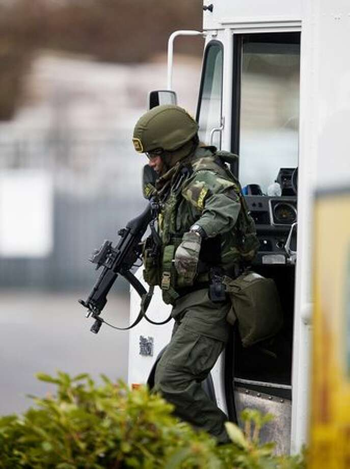 A member of SWAT team gets out of a truck while searching for a suspect Sunday near Lakewood. A gunman shot and killed four Lakewood Police Officers in a Forza Coffee Company shop Sunday morning in what authorities are describing as a targeted attack. Photo: Getty Images