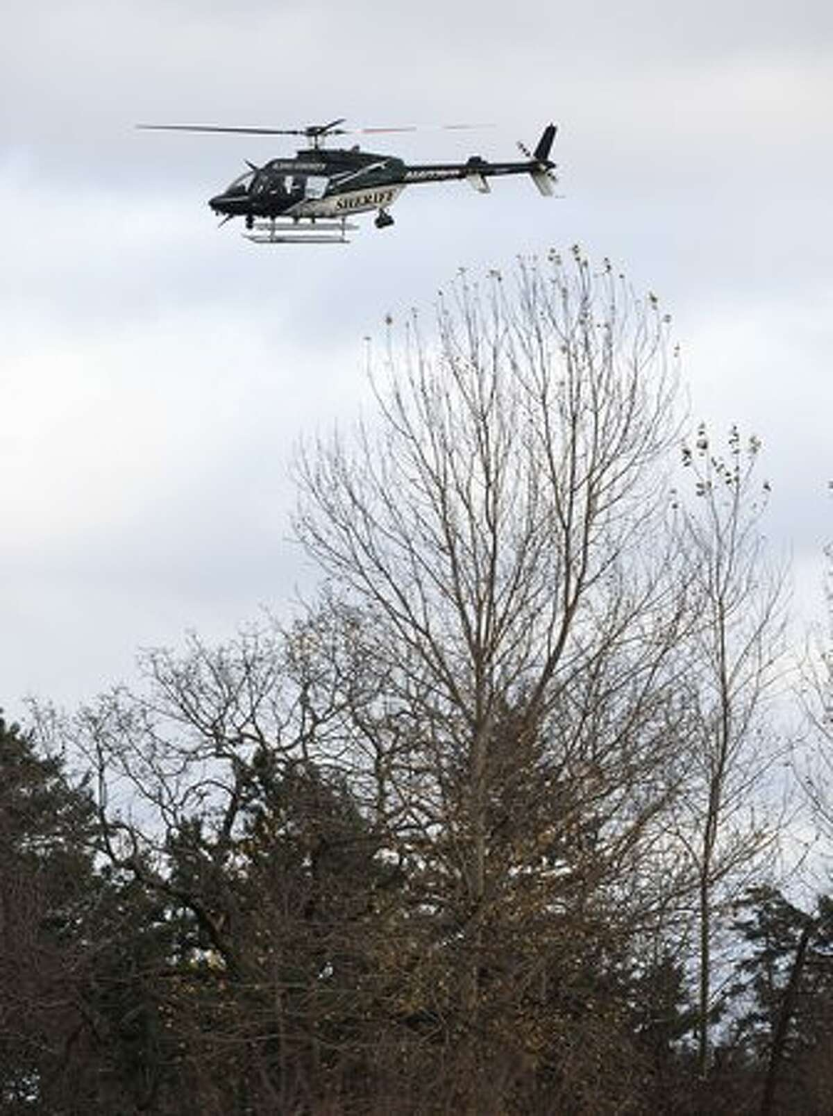 A Pierce County Sheriff helicopter hovers as law enforcement searches for a suspect Sunday near Lakewood. A gunman shot and killed four Lakewood Police Officers in a Forza Coffee Company shop Sunday morning in what authorities are describing as a targeted attack.