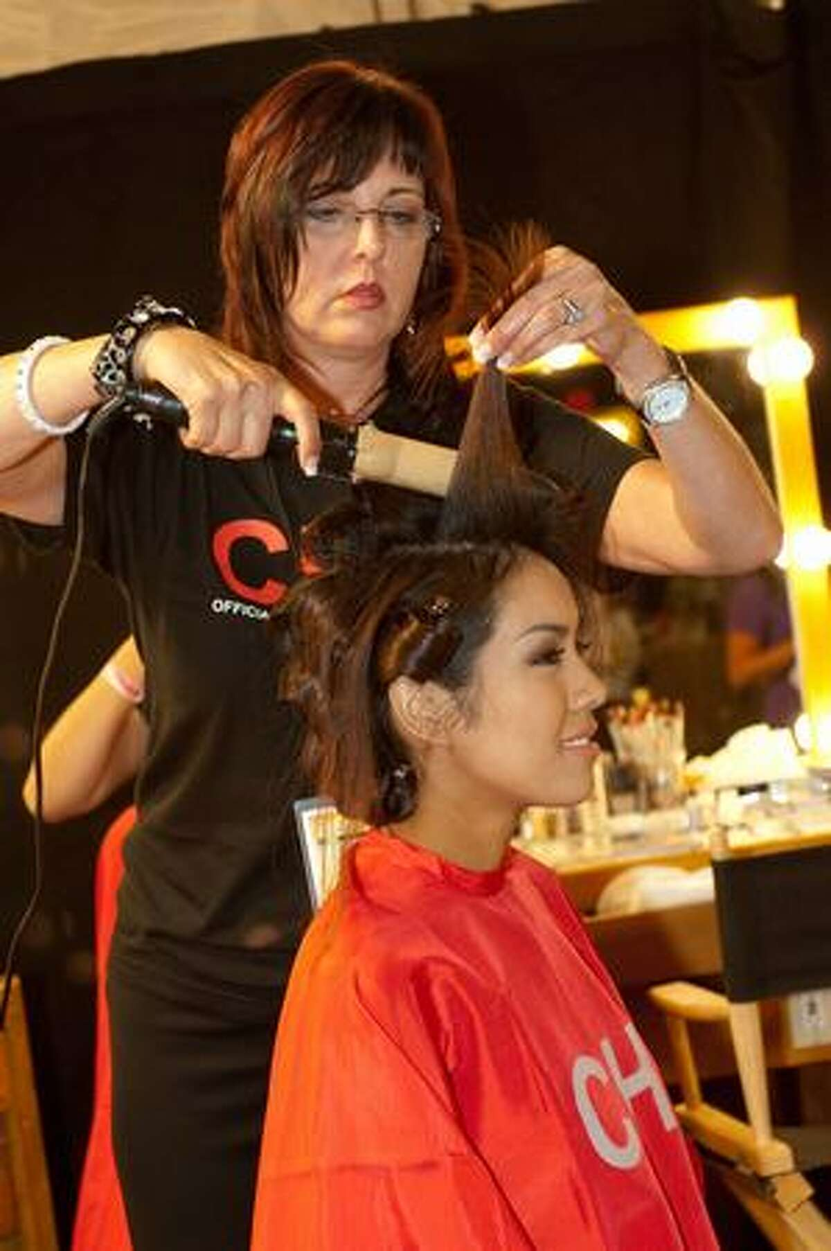 Chutima Durongdej, Miss Thailand, works with hairstylist Angela Leschper as she starts the registration and fitting process.