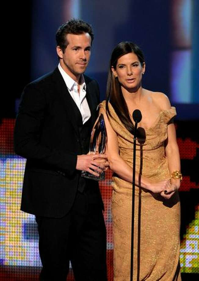 "Actor Ryan Reynolds (L) and actress Sandra Bullock accept the Favorite Comedy Movie award for ""The Proposal."" Photo: Getty Images"