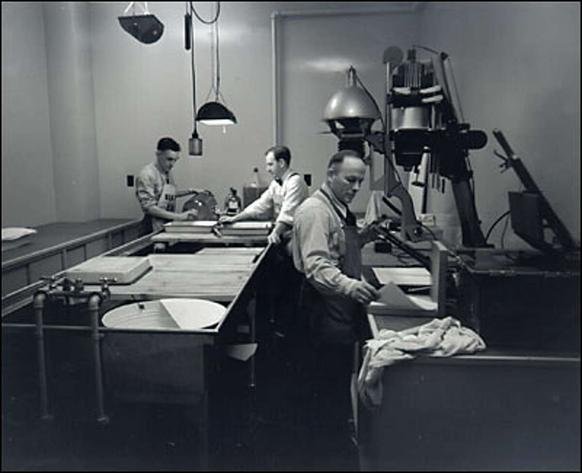 P-I photography department, December 1948. Harvey Davis, Dick Cameron and Stu Hertz set up shop in the new darkroom at the P-I building at 6th Avenue and Wall Street.