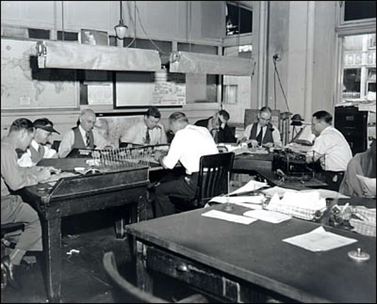 P-I Copy Desk , 1949. The news editor sits at the table, the