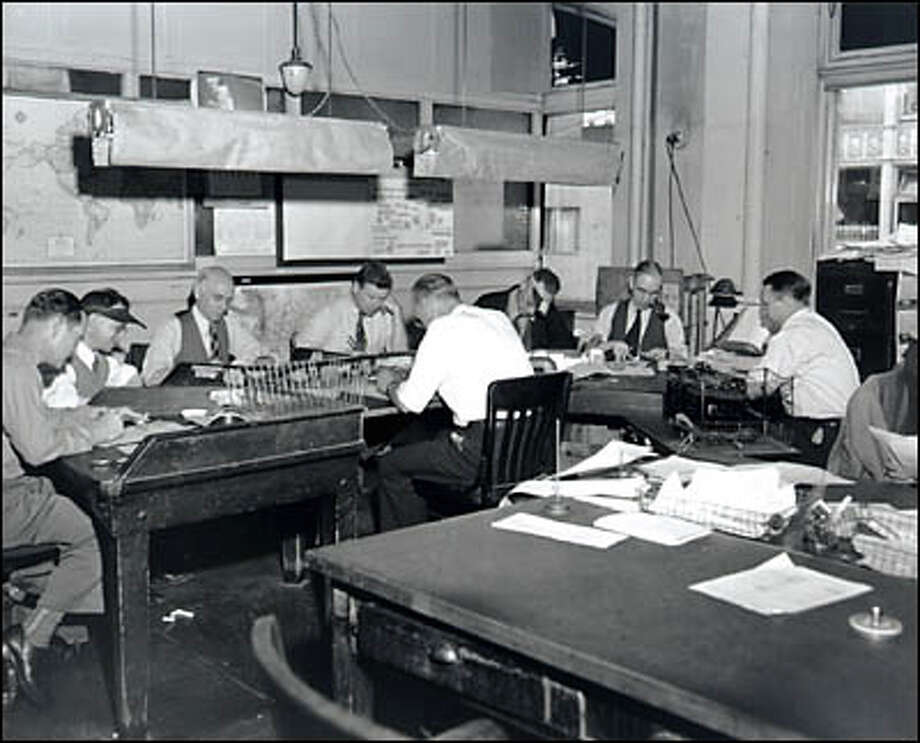 "P-I Copy Desk , 1949. The news editor sits at the table, the ""dealer"" (Roy Goodwin) faces the row of copy editors, identified as: Abe Cohen (2nd from left), Jack MacPherson, Joe Frisino, Bill Gardiner, Monte Snow, and Jack Hart. Photo: Seattle Post-Intelligencer"