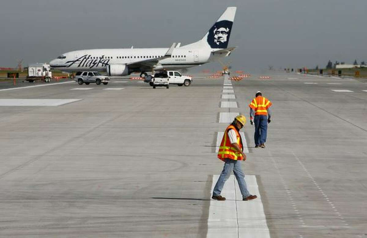 Workers inspect the concrete on runway 34R/16L at Sea-Tac Airport, one of the final steps to reopening the primary landing and takeoff runway at the airport after an extensive rebuild. The 11,901 root runway is slated to begin serving airplanes on September 27th. Photographed on September 21, 2009.