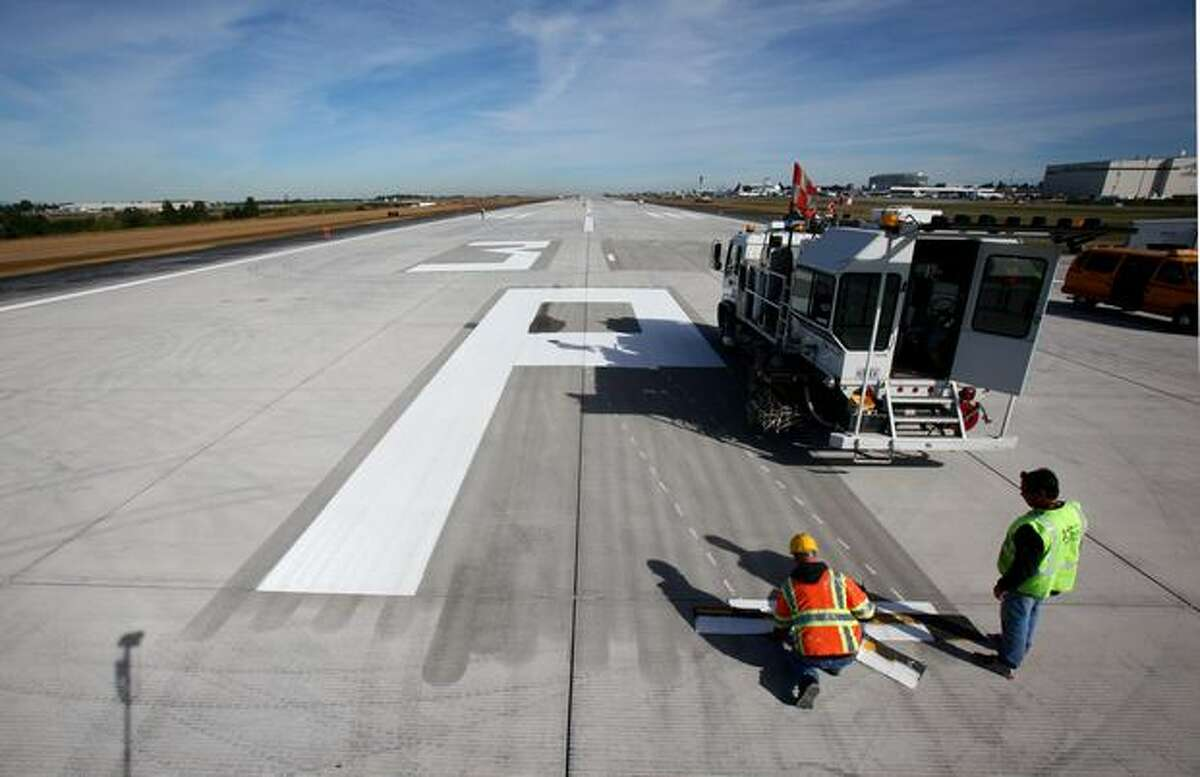 Workers paint a giant 'R' onto runway 34R/16L at Sea-Tac Airport, one of the final steps to reopening the primary landing and takeoff runway at the airport after an extensive rebuild. The 11,901 root runway is slated to begin serving airplanes on September 27th. Photographed on September 21, 2009.