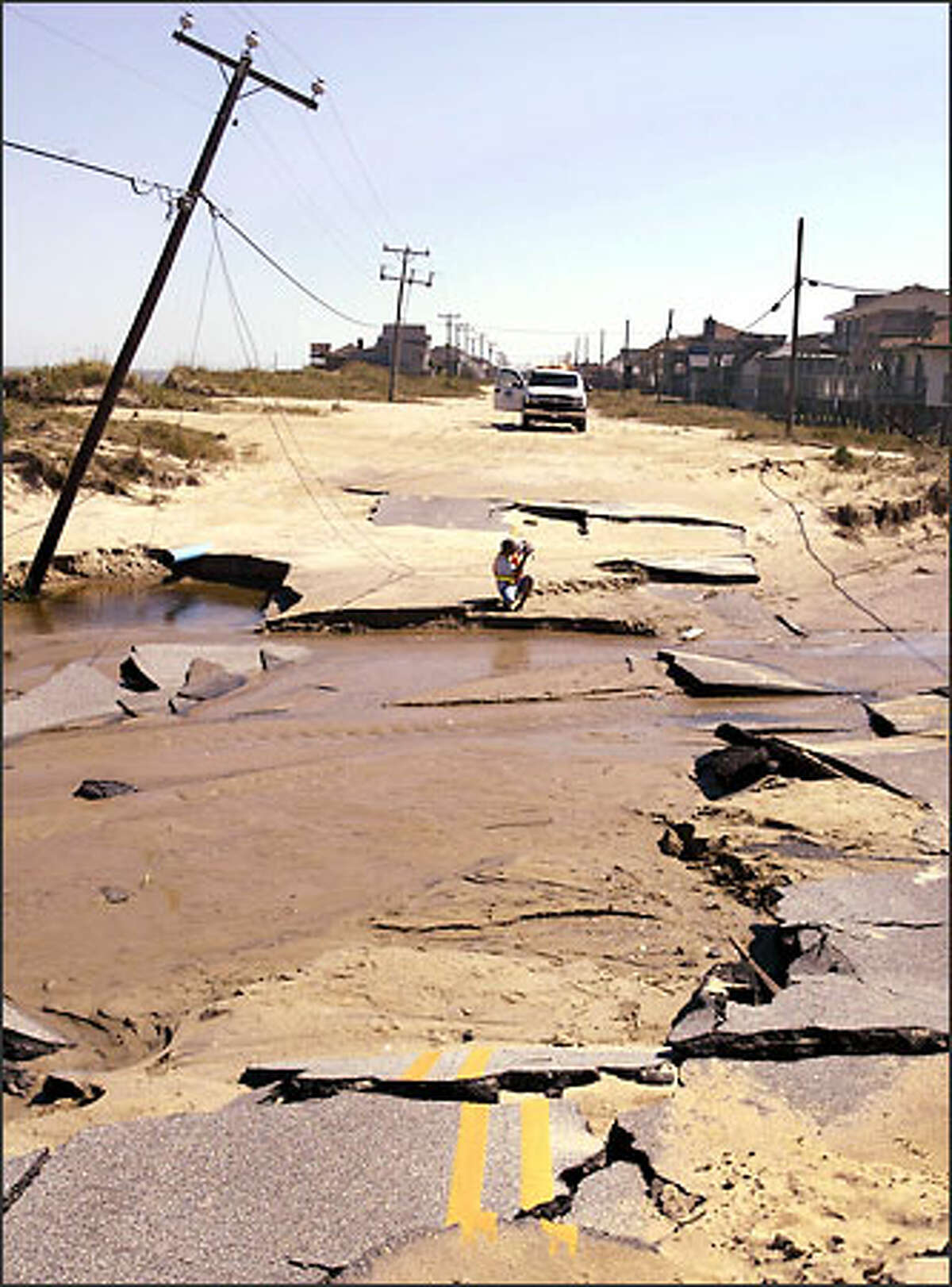 A Dare County official photographs damage done to North Carolina Highway 12 by Hurricane Isabel in Kitty Hawk, N.C. (AP Photo/Bob Jordan)