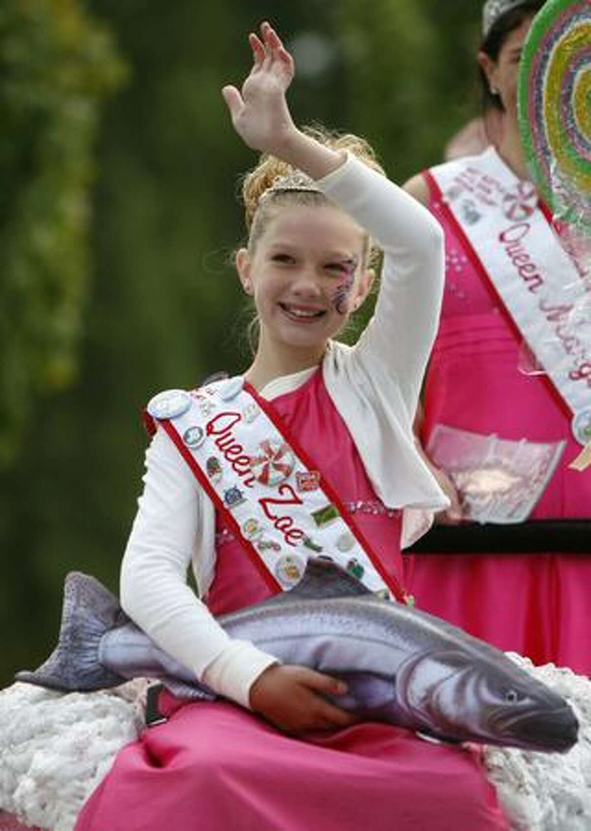 A member of the West Seattle Hi-Yu royalty waves to the crowd during the Issaquah Salmon Days Festival parade.