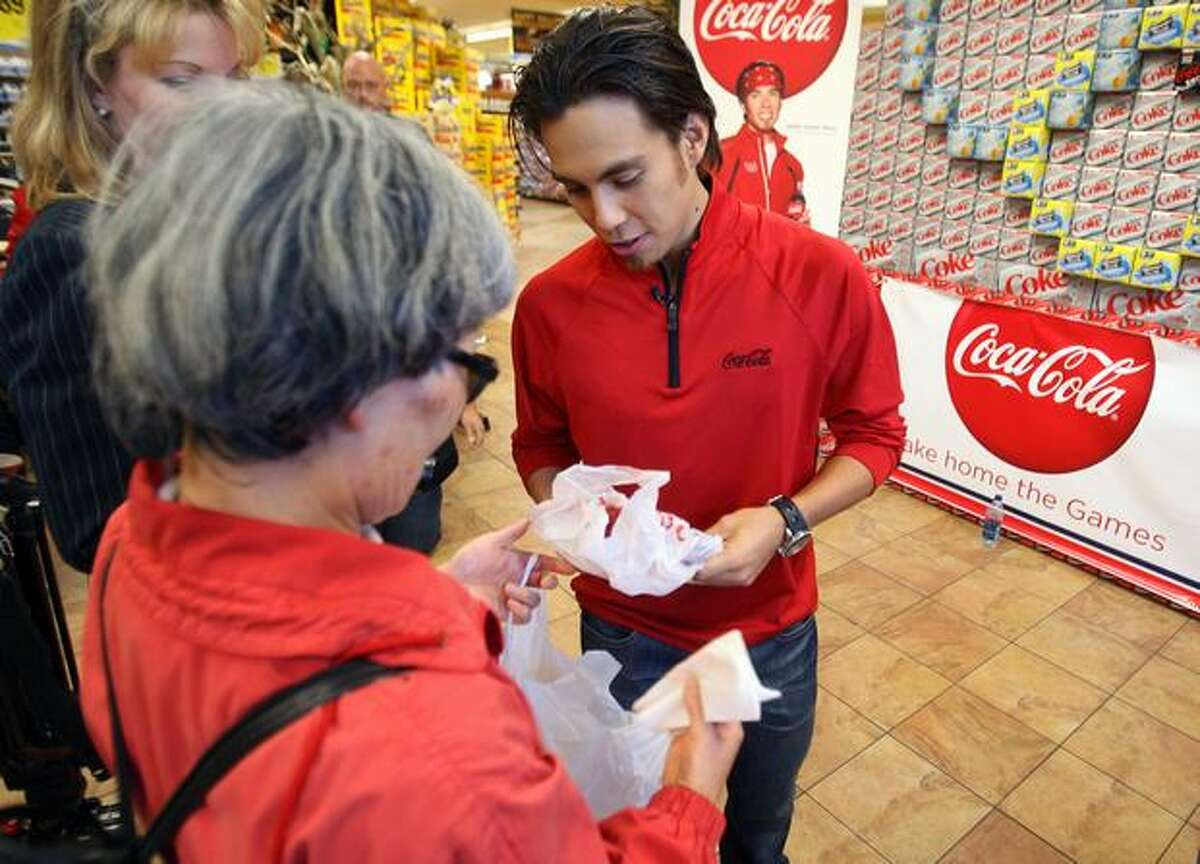 Olympic speed skater Apolo Ohno receives a gift from his junior high school teacher, Chizuko Smith, during the Olympic Winter Games promotional event by Coca-Cola at the University Village QFC Oct. 9.