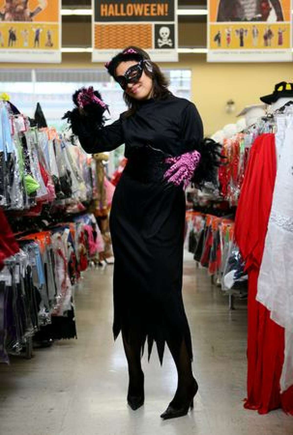 """""""Catwoman"""" -- Gloves, ears (new) $5.99; mask, $1.99; fishnet stockings, $2.99; dress, $4.99. Photographed at Value Village in Seattle."""