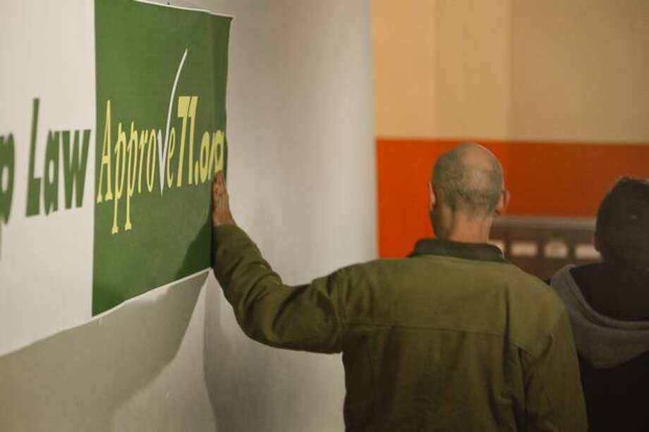 A man touches a sign at the approve Referendum 71 party. Photo: Braden VanDragt, Seattlepi.com