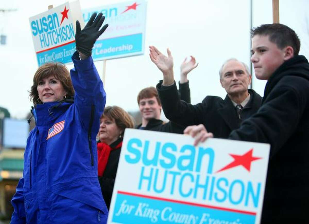 Before she became state GOP chairman, Susan Hutchison ran for King County Executive in 2009. She waves to passing motorists near University Village on election day. Seattle votes beat her.
