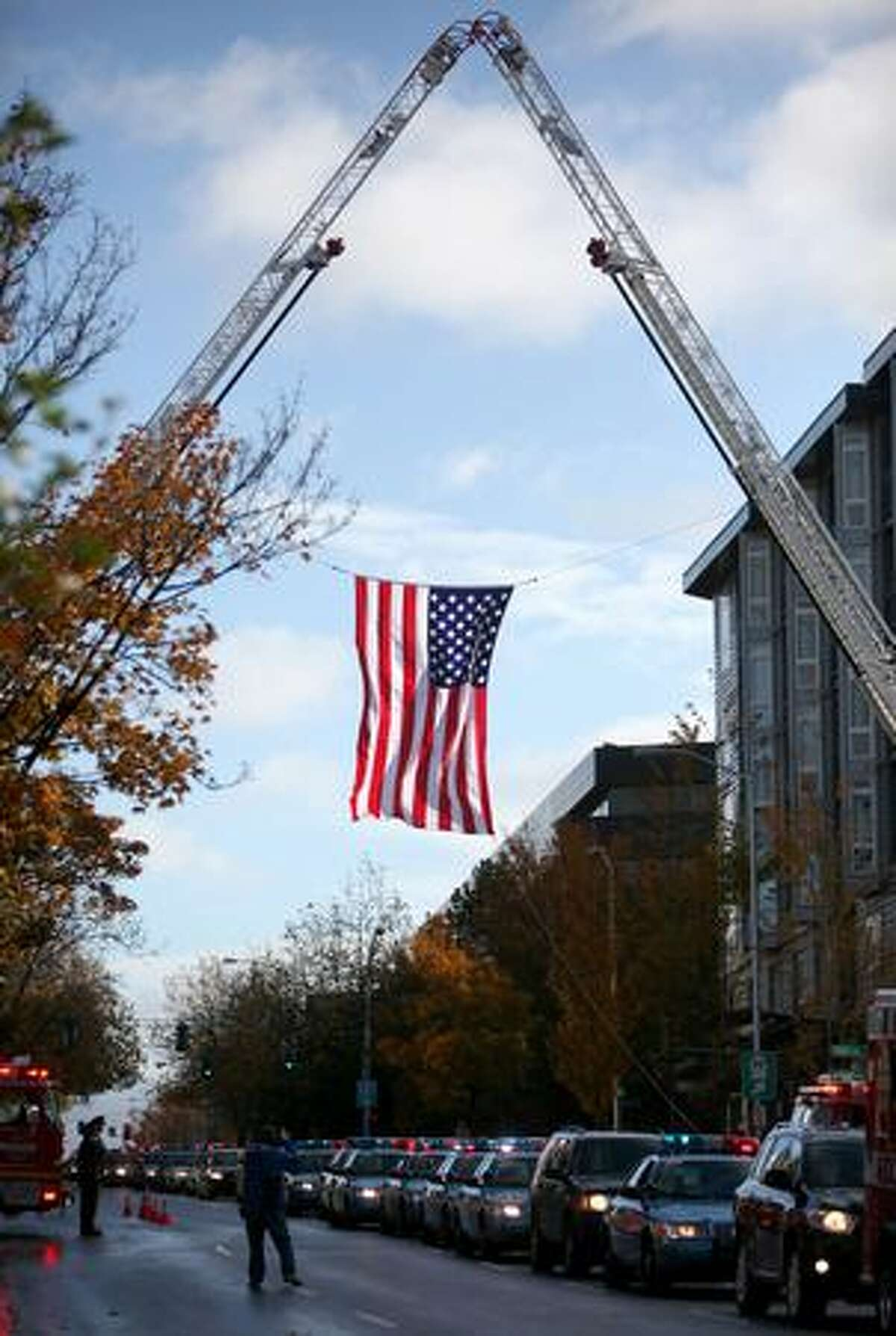 A flag hangs overhead as the memorial procession for Seattle Police Officer Tim Brenton approaches KeyArena.