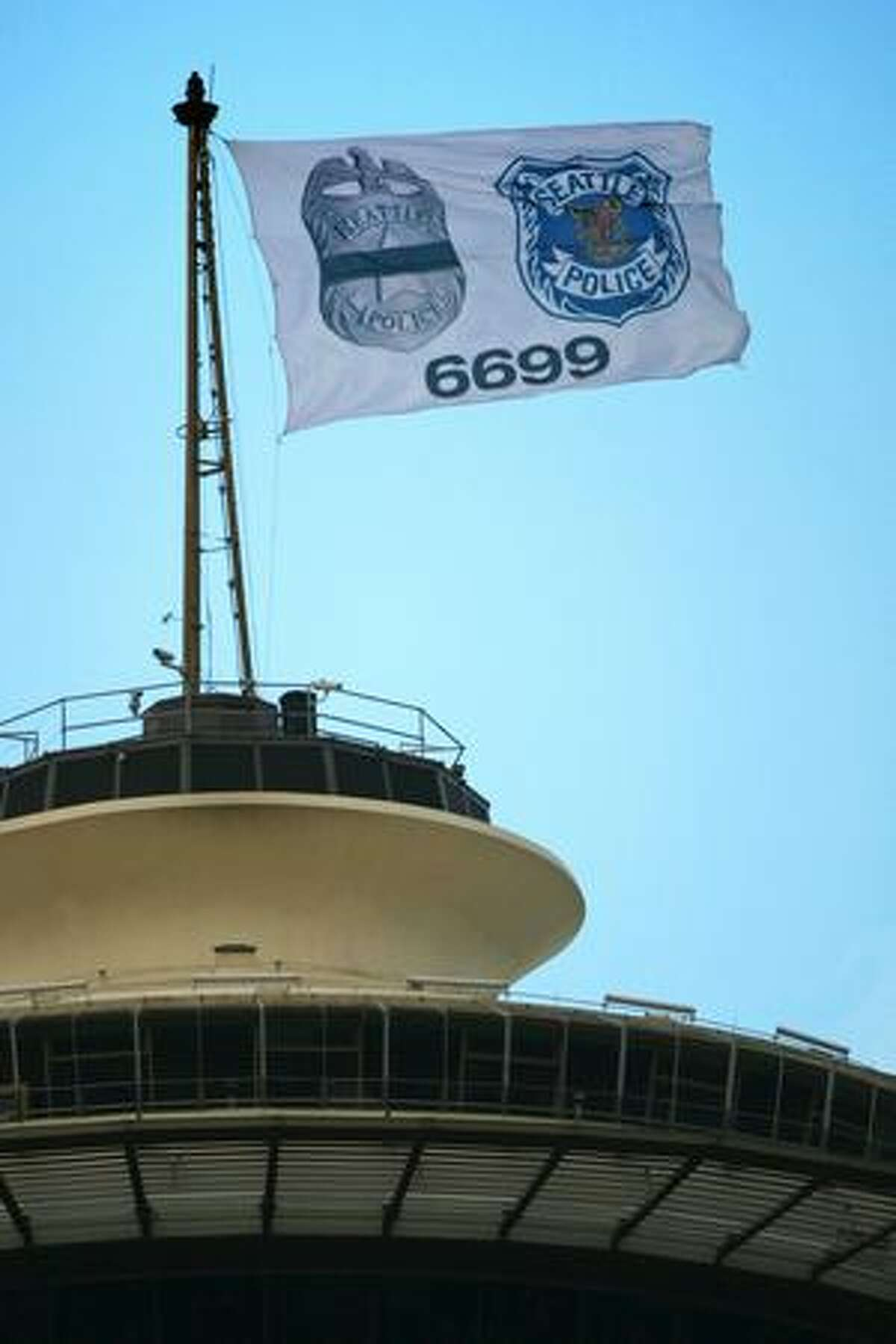 A special flag on top of the Space Needle honors slain Seattle Police Officer Tim Brenton. The flag shows a Seattle Police Department shield, an image of a badge covered by black mourning tape and Brenton's badge number.