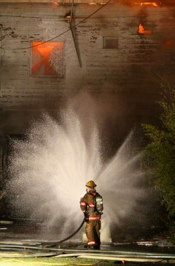 Firefighters from Shoreline, Kirkland, Bothell, Northshore, Seattle, and other departments battle a three-alarm fire in a vacant building on Aurora Avenue North in Shoreline. The fire, which burned for hours, shut down traffic on Aurora through the night. Photo: Joshua Trujillo, Seattlepi.com