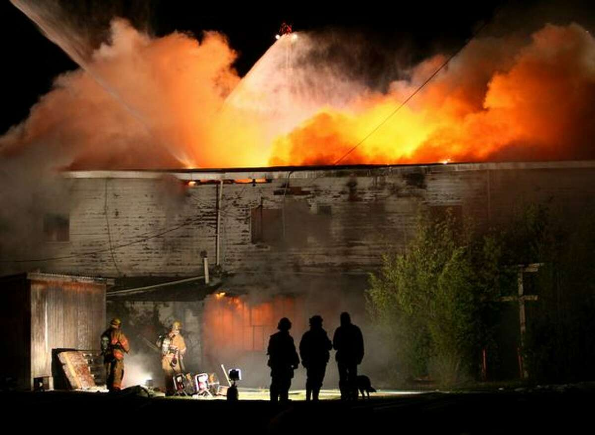 Firefighters from Shoreline, Kirkland, Bothell, Northshore, Seattle, and other departments battle a three-alarm fire in a vacant building on Aurora Avenue North in Shoreline. The fire, which burned for hours, shut down traffic on Aurora through the night.