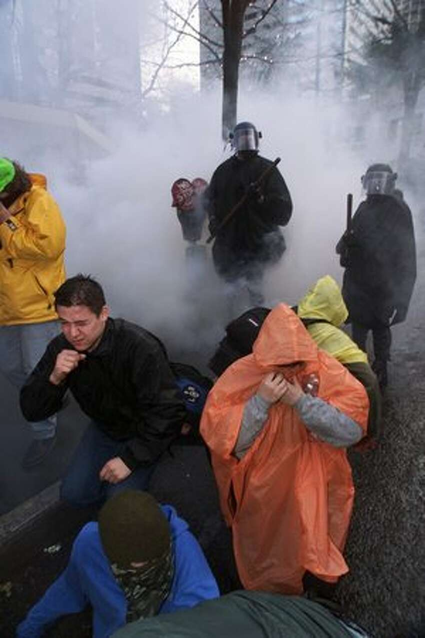 People react to a cloud of tear gas while protesting the WTO on Nov. 30, 1999.