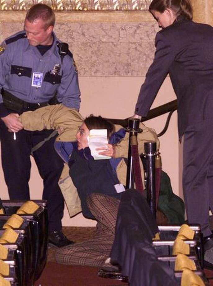 A protester, who said she was from San Francisco and demanded a dialogue on environmental issues, is dragged out of the Paramount Theater where the WTO inaugural session was scheduled on Nov. 30, 1999. The chaos in the streets stopped the event from happening. Photo: Seattle Post-Intelligencer