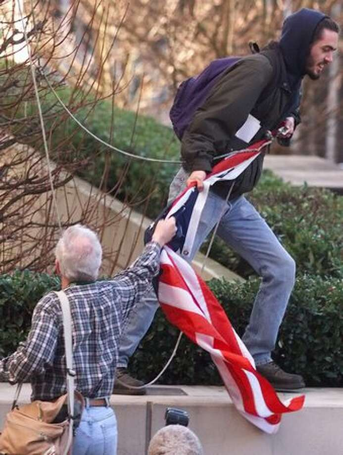 WTO protester Bob Patrick of Ballard tries to save the U.S. flag from being desecrated by another protester on Dec. 2, 1999. The flag was taken from the flagpole outside the King County Jail. Patrick and other protesters lead a successful effort, after some scuffling, to return the flag up the pole. (Photo by Mike Urban) Photo: Seattle Post-Intelligencer