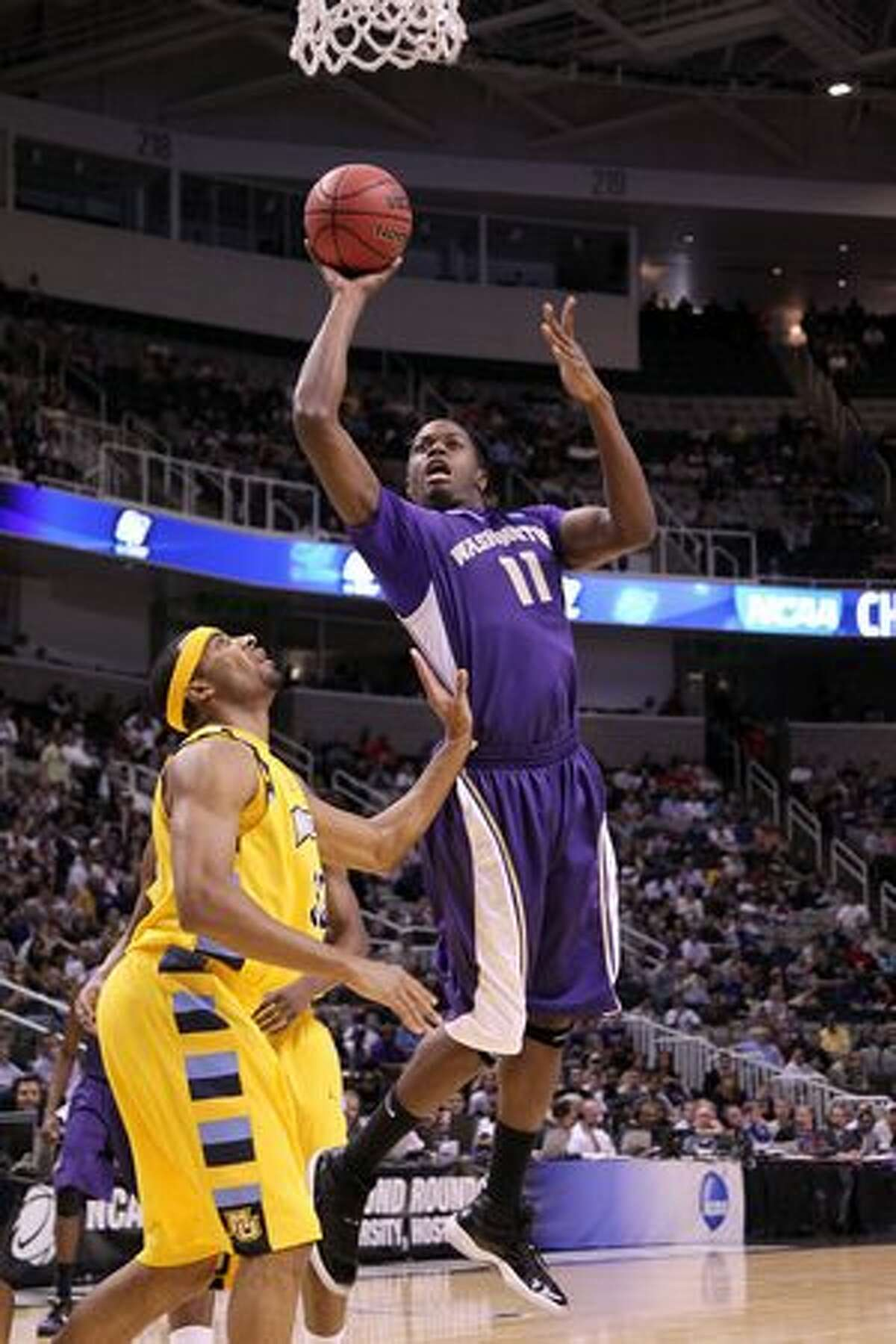 Forward Matthew Bryan-Amaning #11 of the Washington Huskies goes up for a shot against the Marquette Golden Eagles.