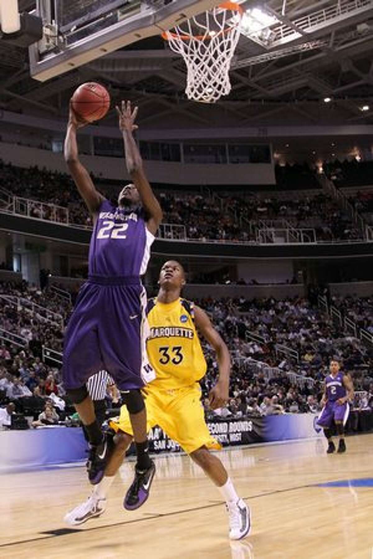 Forward Justin Holiday #22 of the Washington Huskies goes up for a shot against the Marquette Golden Eagles.