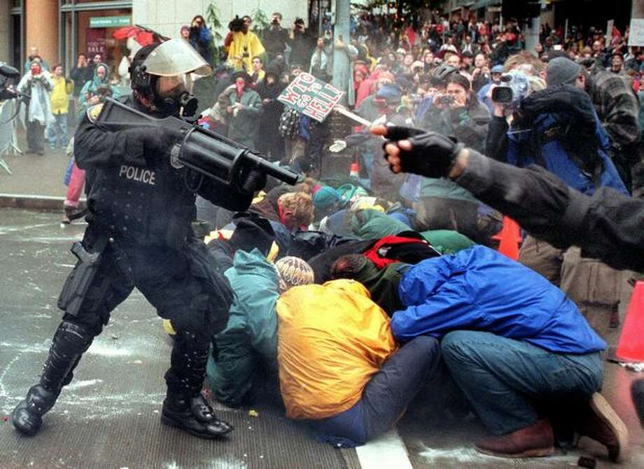 A Seattle Police officer fires his weapon point blank into a group of demonstrators attempting to prohibit access to the WTO at the intersection of Sixth Avenue and Union Street on Nov. 30, 1999, outside the Seattle Sheraton. Police first informed the demonstrators that they were in violation of an order to disperse. (Photo by Paul Joseph Brown) Photo: Seattle Post-Intelligencer