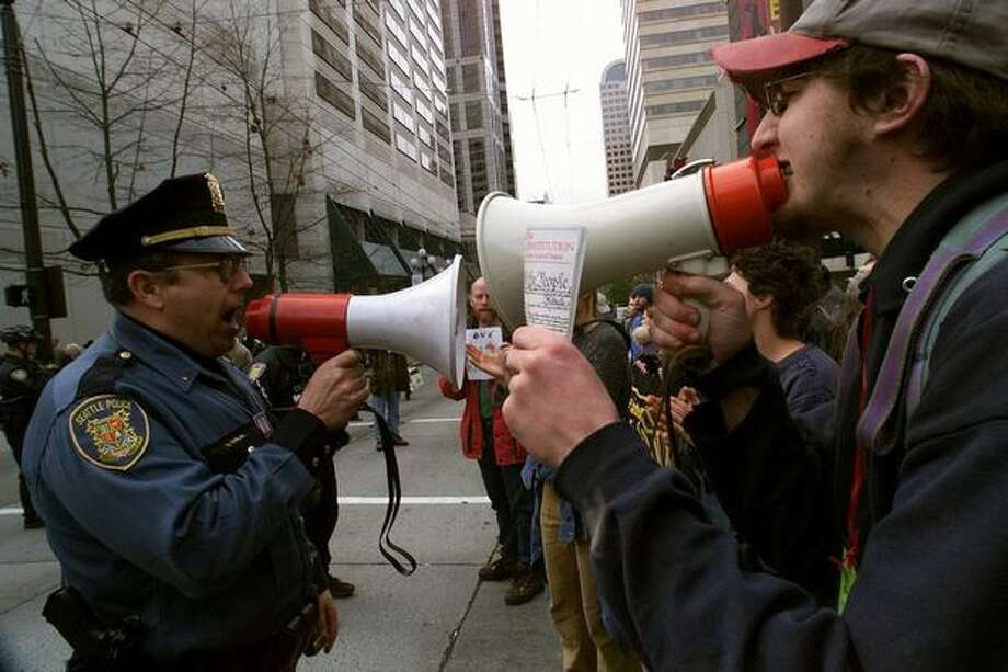 protester Douglas Mackar, right, with a copy of the Constitution in his hand, and Seattle Police Lt. Daniel Whelan have conflicting messages on their bullhorns during the WTO protest on Nov. 29, 1999. (Photo by Dan DeLong) Photo: Seattle Post-Intelligencer