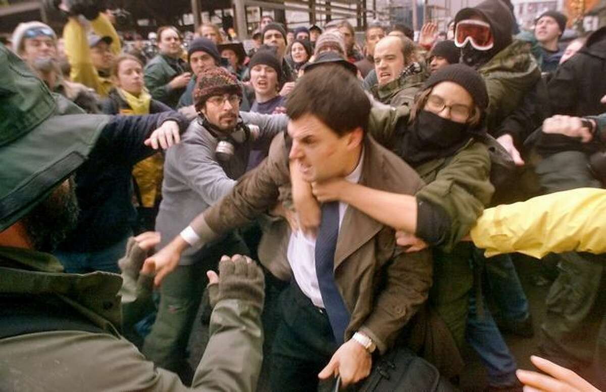A WTO delegate is mauled by protestors at Seventh Avenue and Union as they try to prevent his access to the Washington State Convention & Trade Center on Nov. 30, 1999. (Photo by Mike Urban)