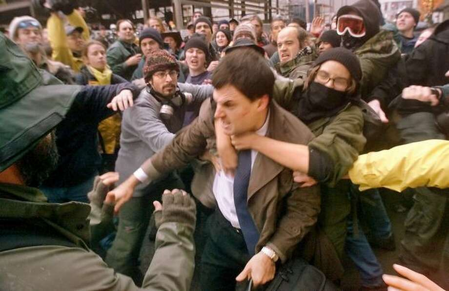 A WTO delegate is mauled by protesters at Seventh Avenue and Union as they try to prevent his access to the Washington State Convention & Trade Center on Nov. 30, 1999. (Photo by Mike Urban) Photo: Seattle Post-Intelligencer