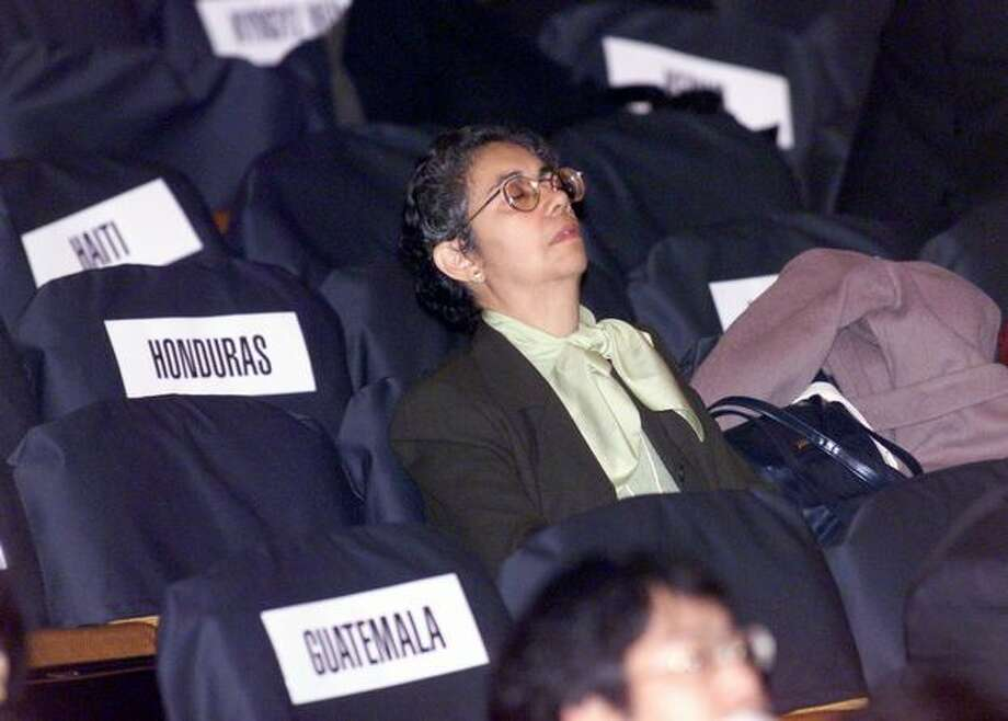A WTO delegate takes a nap as she waits for the inaugural session to begin at the Paramount Theater on Nov. 30, 1999. The event was cancelled after three hours of waiting for other delegates to get through throngs of protesters in the streets of Seattle. (Photo by Grant M. Haller) Photo: Seattle Post-Intelligencer