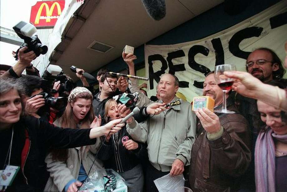 Bill Christison, president of the National Family Farm Coalition, and Jose Bove, a French farmer and anti-WTO activist, celebrate their protest against McDonald's with French wine, American and French cheese, and French bread. The demonstration shut down the intersection of Third Avenue and Pine Street in Seattle. (Photo by Paul Joseph Brown) Photo: Seattle Post-Intelligencer