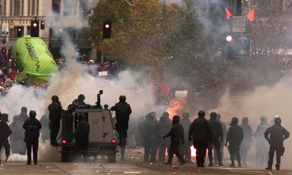 Seattle Police try to disperse a crowd of WTO protestors on Nov. 30, 1999, as they light a bonfire o