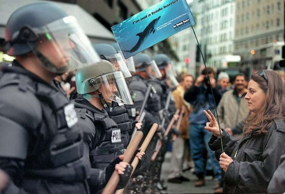 Erin O'Connell of Seattle stands in silent, nonviolent confrontation with a line of Seattle Police officers at the corner of Second Avenue and Pine Street. (Photo by Paul Joseph Brown) Photo: Seattle Post-Intelligencer