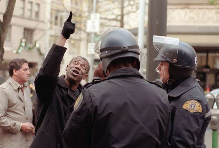 A man who said he was a downtown office worker tries to convince police to allow him to pass on Dec. 3, 1999. (Photo by Rick Giase) Photo: Seattle Post-Intelligencer