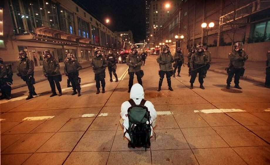 A lone WTO protester sits in front of a line of King County sheriff's deputies outside Benaroya Hall on Nov. 30, 1999, as police clear the downtown area. Photo: Seattle Post-Intelligencer