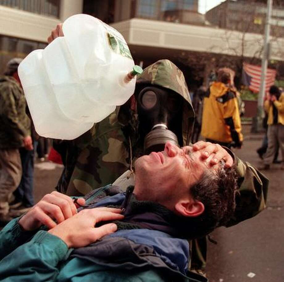 A protester gets relief after getting hit by pepper spray and tear gas on Nov. 30, 1999. (Photo by Paul Joseph Brown) Photo: Seattle Post-Intelligencer