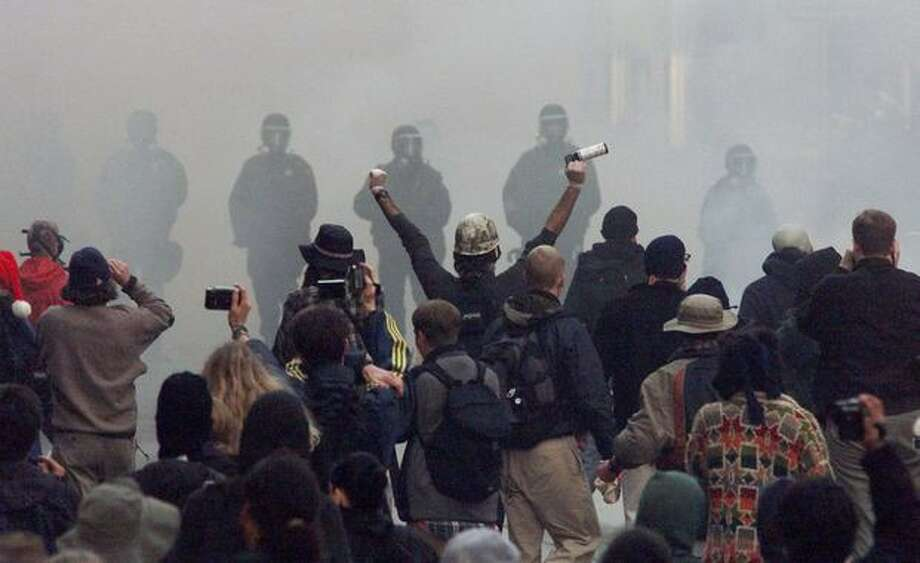 Prostesters confront police through a cloud of tear gas at Fourth Avenue and Pine Street on Nov. 30, 1999. Photo: Seattle Post-Intelligencer