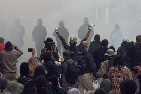 Prostestors confront police through a cloud of tear gas at Fourth Avenue and Pine Street on Nov. 30, 1999. (Photo by Mike Urban)