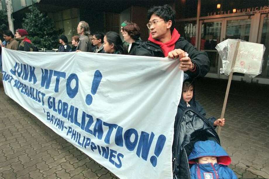 Wil Depusoy attempts to shield his daughters Gabriela, 4, and Apolinario, 1, from the wind and rain while holding a sign protesting the WTO in front of the Seattle Municipal Building. Photo: Seattle Post-Intelligencer