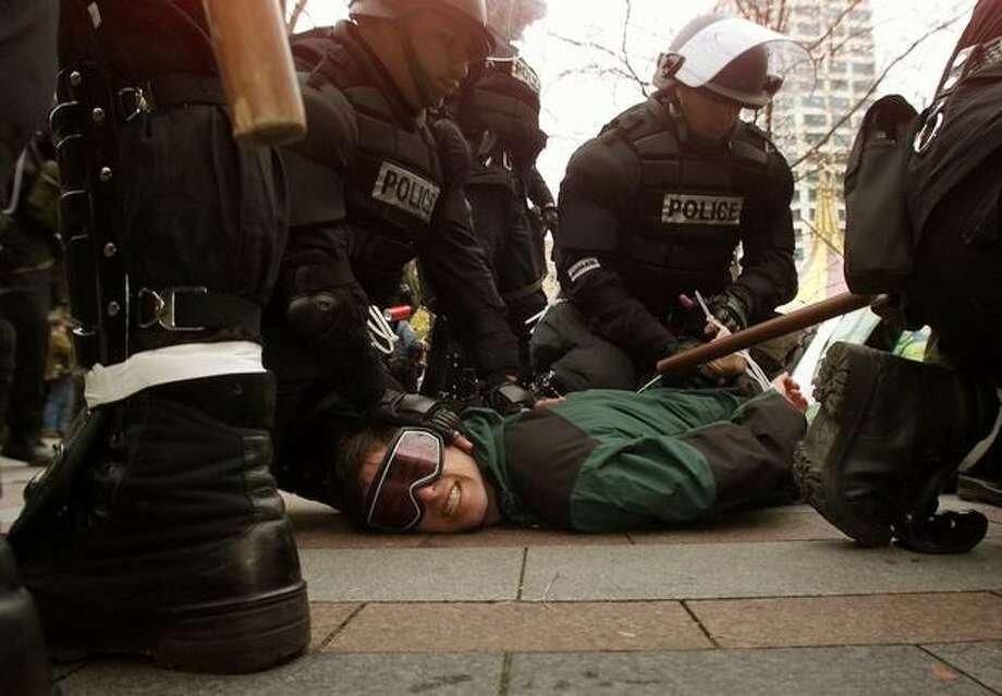 A WTO protester is arrested and cuffed by Seattle Police officers on the paving stones of Westlake Park on Dec. 1, 1999, after protesters attempted a peaceful sit-down demonstration at the park. (Photo by Mike Urban) Photo: Seattle Post-Intelligencer