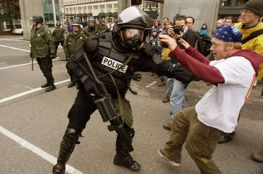 A Seattle police officer shoves protester Jody Hutchinson as police march down Virginia Street on Dec. 1, 1999.