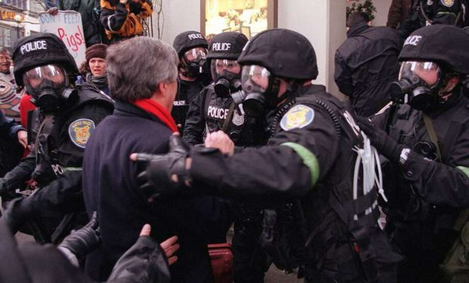Officers in riot gear help a delegate get through the crowd of protesters on Nov. 30, 1999. (Photo by Paul Joseph Brown) Photo: Seattle Post-Intelligencer
