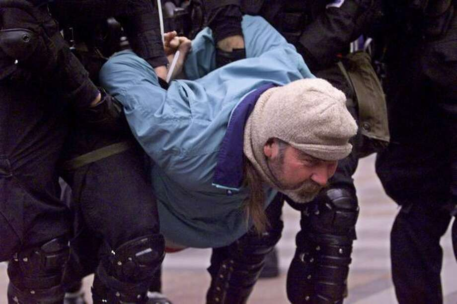 "Dec. 1, 1999: Police enforce a ""no protest zone"" around the World Trade Organization meetings and arrest hundreds of demonstrators. Photo: Seattle Post-Intelligencer"