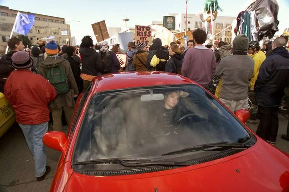 Fran Swak of Seattle tries in frustration to get home from work along Denny Way as protesters shut down the street on their way to Victor Steinbrueck Park on Dec. 2, 1999. (Photo by Mike Urban) Photo: Seattle Post-Intelligencer