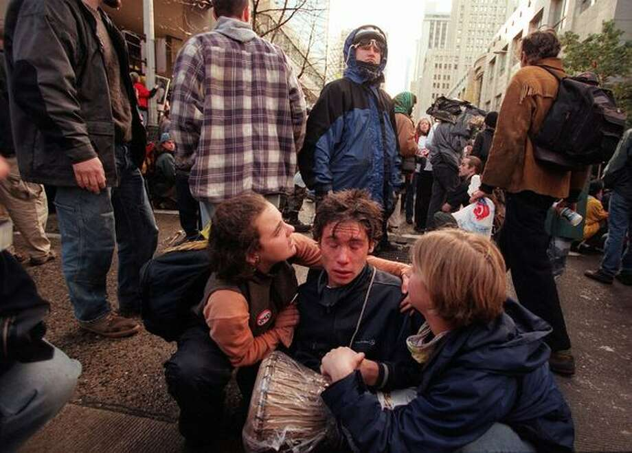 WTO protesters comfort a fellow demonstrator as he recovers from tear gas on Nov. 30, 1999. (Photo by Paul Joseph Brown) Photo: Seattle Post-Intelligencer