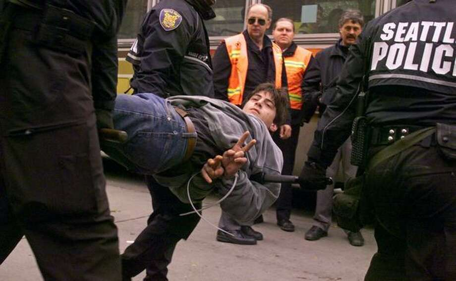 "WTO protesters performed a peaceful sit-down demonstration in Westlake Park. A new ""no protest"" rule let police arrest these protesters even if they weren't blocking traffic. Here, a protester flashes the peace symbol to the crowd as officers carry him to a waiting Metro bus on Dec. 1, 1999. Photo: Seattle Post-Intelligencer"