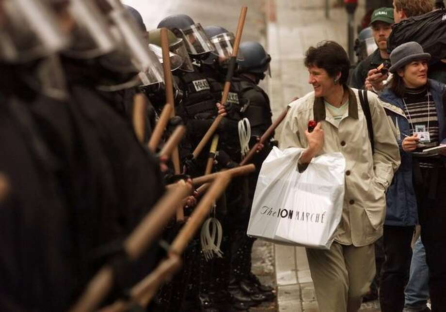 A Bon Marche shopper gives a smile to a row of riot police lined up on Sixth Avenue on Dec. 1, 2009. Photo: Seattle Post-Intelligencer