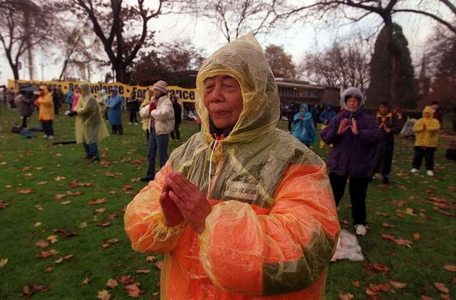 A Falun Gong follower meditates in Denny Park in protest of the WTO conference Nov. 30, 1999. (Photo by Rick Giase) Photo: Seattle Post-Intelligencer