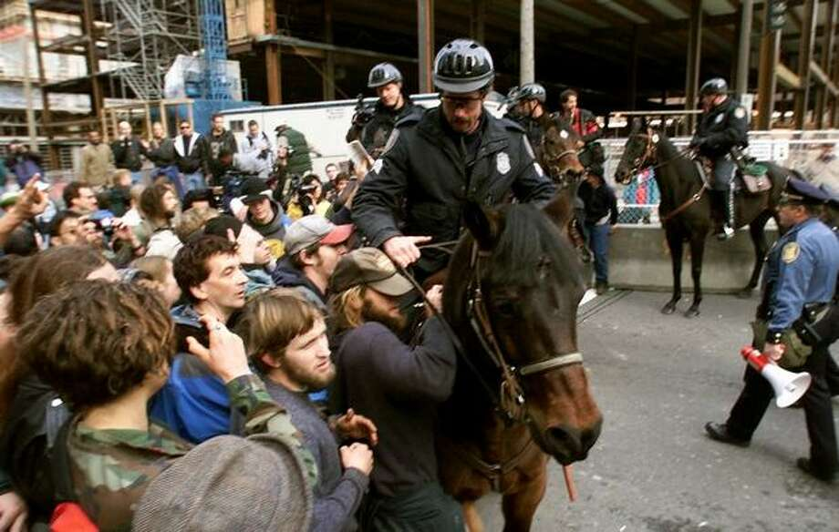 Seattle Police officers on horseback push WTO protesters back near the Washington State Convention & Trade Center on Nov. 29, 1999. (Photo by Dan DeLong) Photo: Seattle Post-Intelligencer